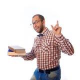 El individuo divertido muestra que los libros son muy importantes en vida Foto de archivo