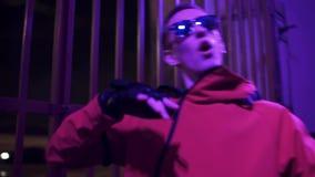 El individuo divertido vestido en ropa y gafas de sol rojas del deporte canta activamente en la noche almacen de video