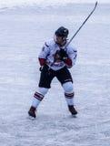El individuo durante un partido del hockey con el palillo aumentado imagen de archivo