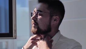 El individuo elegante adentro endereza el cuello de su situación de la camisa cerca de la ventana Eso es un marco agradable almacen de metraje de vídeo
