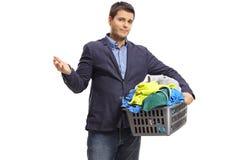 El individuo elegante infeliz que sostenía una cesta de lavadero llenó de ropa imagen de archivo libre de regalías