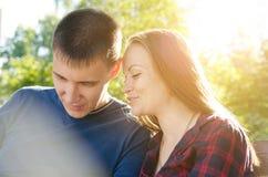El individuo en camiseta azul y la muchacha en camisa de tela escocesa están hablando mientras que se sienta en banco en el parqu imágenes de archivo libres de regalías