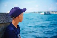 El individuo en el casquillo se está sentando mirando el mar fotografía de archivo libre de regalías