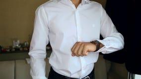 El individuo en la camisa blanca ajusta el reloj y el primer de las mancuernas