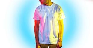 El individuo en la camiseta blanca en blanco, soporte, sonriendo en un fondo blanco, mofa para arriba, espacio libre, logotipo, d Fotografía de archivo