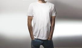El individuo en la camiseta blanca en blanco, soporte, sonriendo en un fondo blanco, mofa para arriba, espacio libre, logotipo, d Imagen de archivo libre de regalías