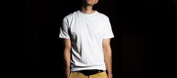 El individuo en la camiseta blanca en blanco, soporte, sonriendo en un fondo negro, mofa para arriba, espacio libre, logotipo, di Fotos de archivo