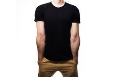 El individuo en la camiseta negra, espacio en blanco, sonriendo en un backgrou blanco Foto de archivo