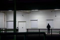 El individuo en la capilla se coloca en la noche cerca de la pared fotos de archivo libres de regalías
