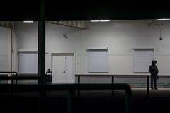 El individuo en la capilla se coloca en la noche cerca de la pared foto de archivo libre de regalías