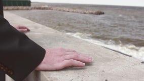 El individuo en la chaqueta pone sus manos en el embarcadero cerca del mar almacen de metraje de vídeo