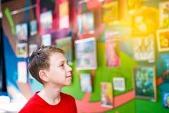 El individuo en la exposición de pinturas y de fotografías mira cuidadosamente la pintura y disfruta de arte Imagen de archivo