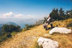El individuo en las montañas en la bahía del fondo en Montenegro Un individuo se sienta en un banco en las montañas en la bahía d foto de archivo