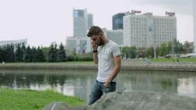 El individuo en ropa casual en un banco del río está invitando al teléfono celular metrajes