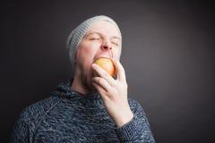 El individuo en el sombrero come Apple rojo en un fondo negro en el estudio fotos de archivo libres de regalías
