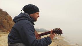 El individuo en el sombrero hecho punto se sienta en una piedra y toca la guitarra jugar la opinión de la guitarra del individuo  almacen de metraje de vídeo