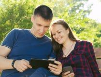 El individuo en una camiseta azul y la muchacha en camisa de tela escocesa están mirando sus fotos del viaje imagenes de archivo