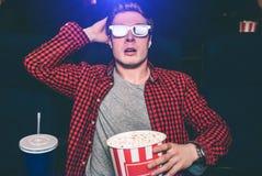 El individuo es película del watchin en pasillo del cine Él ha puesto su mano sobre la cabeza Él está sosteniendo una cesta con p imagen de archivo
