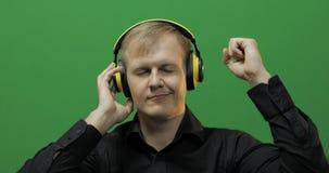 El individuo escucha la m?sica en auriculares amarillos inal?mbricos y danzas Pantalla verde imagenes de archivo