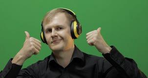 El individuo escucha la m?sica en auriculares amarillos inal?mbricos y danzas Pantalla verde fotografía de archivo libre de regalías