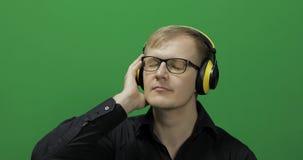 El individuo escucha la m?sica en auriculares amarillos inal?mbricos y danzas Pantalla verde fotos de archivo libres de regalías