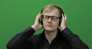 El individuo escucha la m?sica en auriculares amarillos inal?mbricos y danzas Pantalla verde foto de archivo