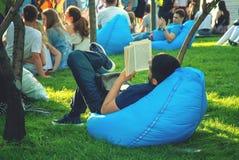 El individuo está leyendo un libro en el parque Fotografía de archivo