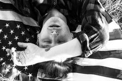 El individuo está mintiendo en la hierba con la bandera americana Fotografía de archivo