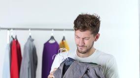 El individuo está sosteniendo la ropa almacen de video