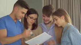 El individuo explica algo en su notebool a sus colegas