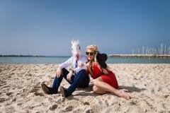 El individuo extraño en traje y máscara divertida se sienta con la muchacha hermosa en vestido rojo Fotos de archivo