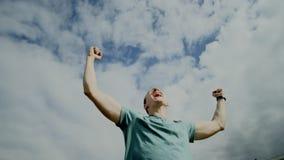 El individuo feliz aumenta sus manos y gritos almacen de metraje de vídeo