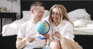 El individuo feliz y la muchacha queridos de los pares que se sientan al lado de la cama están mirando el globo que elige un luga almacen de video