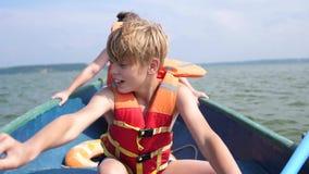 El individuo flota en el barco Adolescente actúa independientemente un barco con la ayuda de los remos Deporte extremo metrajes