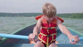 El individuo flota en el barco Adolescente actúa independientemente un barco con la ayuda de los remos Deporte extremo almacen de video