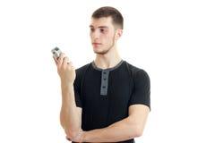 El individuo fuerte joven alto se levanta recto y que sostiene podadoras para afeitar Foto de archivo