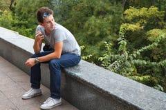 El individuo fuma un cigarrillo que se sienta en un encintado del granito Ciérrese los ojos Fotografía de archivo libre de regalías