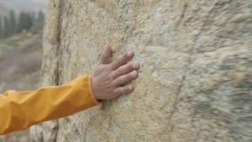 El individuo funciona con su mano sobre la roca almacen de video