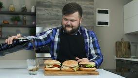 El individuo gordo alegre vierte el refresco carbónico en un vidrio Se preparan las hamburguesas Forma de vida malsana, frita y almacen de video