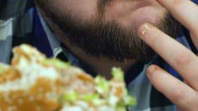 El individuo gordo barbudo de Timelapse muerde una hamburguesa que él cocinó El hombre come la comida hecha en casa Caloría malsa almacen de metraje de vídeo