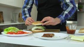 El individuo gordo en un delantal cocina las hamburguesas en casa Todos los ingredientes y productos están en la tabla Forma de v almacen de metraje de vídeo