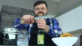 El individuo gordo se sienta en la cocina en la tabla y abre una botella de cerveza con un cuchillo Las patatas fritas están en u almacen de video