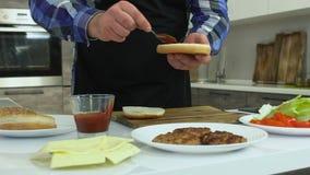 El individuo grueso cocina las hamburguesas en casa El hombre regordete mancha la pasta de tomate en un bollo Forma de vida malsa metrajes