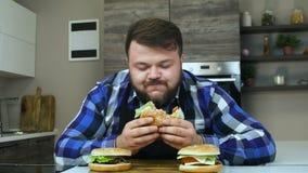 El individuo grueso come y goza de su hamburguesa La persona con una barba come la comida que él cocinó Forma de vida malsana, fr almacen de video