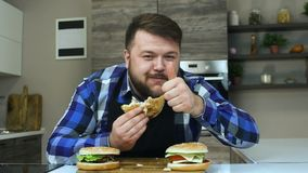 El individuo grueso con una barba come un pedazo de hamburguesa y las demostraciones golpean pesadamente para arriba o tienen gus metrajes