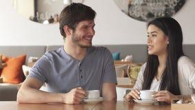 El individuo habla con su amigo femenino en el café almacen de video