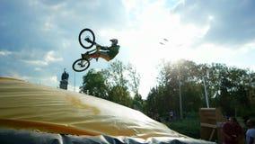 El individuo hace el tailwhip en el bmx, saltando en el trampolín con la bici, los deportes extremos, trucos peligrosos en la bic almacen de video