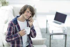 El individuo hermoso con una taza se sienta delante de un ordenador portátil Fotografía de archivo libre de regalías