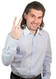 El individuo hermoso cuenta en sus dedos dos aislados Foto de archivo libre de regalías