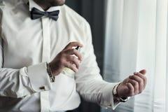 El individuo hermoso está eligiendo perfumes, hombre rico prefiere la cuesta costosa foto de archivo